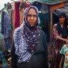 سيّدة يمنية نازحة تقف أمام مأوى مؤقت تعيش به هي وأسرتها الممتدة.