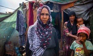 Une Yéménite déplacée se tient devant un abri de fortune qu'elle partage avec sa famille élargie.