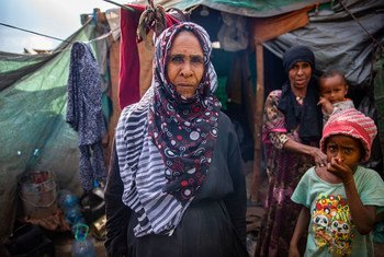 A displaced Yemeni woman stands outside a makeshift shelter that she shares with her extended family.