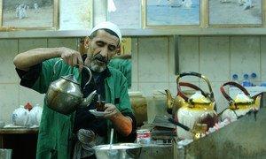 एक व्यक्ति कुवैत की एक कॉफी शॉप में चाय तैयार कर रहा है.