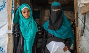 Rania and her eldest daughter, Amani, stand in the entrance to their home in a camp for internally displaced people in Lahj, Yemen.