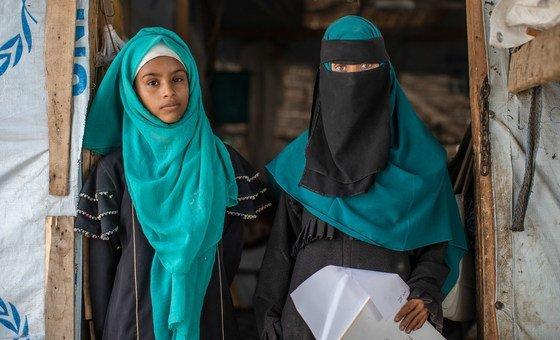 رانيا وابنتها أماني تقفان على مدخل خيمتهما في مخيم للنازحين في لحج باليمن.