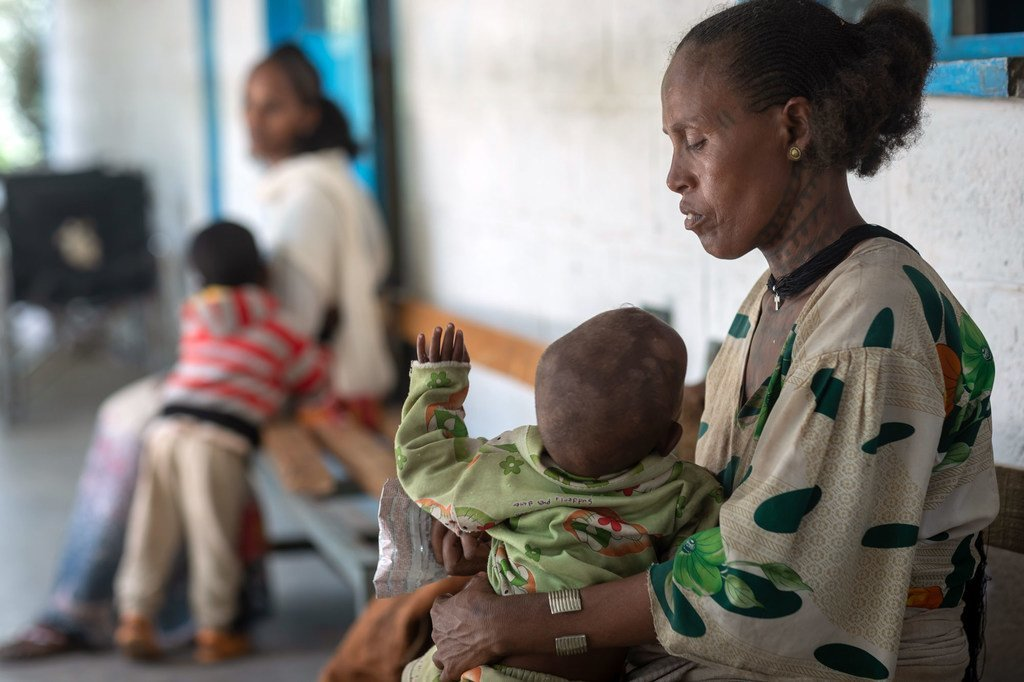 Mama akiwa amembeba mwanae wa kiume mwenye umri wa mwaka mmoja anayeugua utapiamlo katika kituo cha afya huko Tigray nchini Ethiopia.