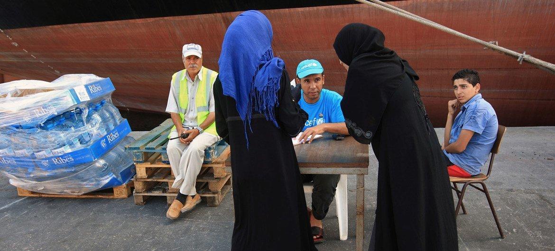 من الأرشيف: امرأتان تطلبان الماء من موظف في اليونيسف في ميناء طرابلس، عاصمة ليبيا.