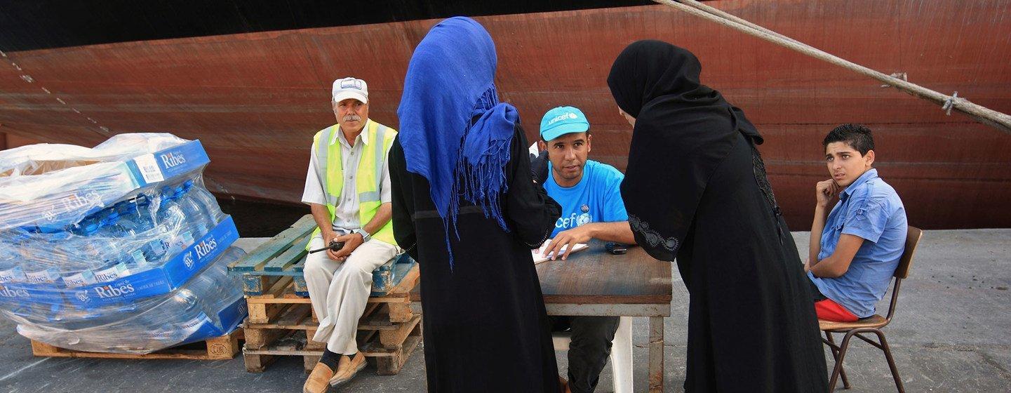 Un employé de l'UNICEF écoute deux femmes qui demandent de l'eau dans le port de Tripoli, la capitale de la Libye. (archives)