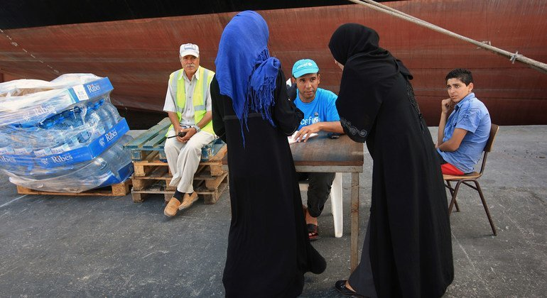 Un trabajador de UNICEF observa cómo dos mujeres piden agua en el puerto de Trípoli, la capital de Libia.