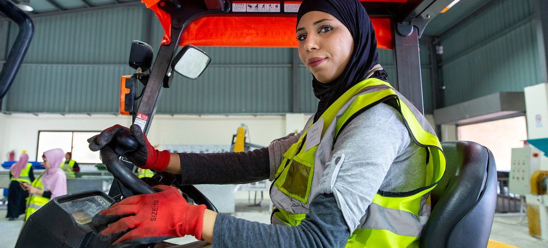 一名妇女在约旦北部的一家回收工厂工作。
