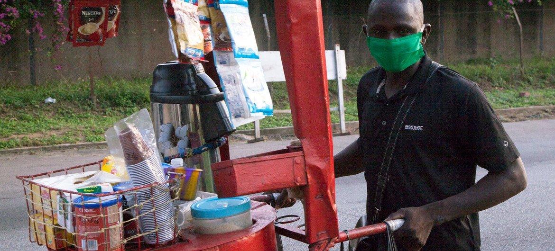 Un vendedor informal de Costa de Marfil utiliza mascarilla para protegerse del coronavirus.