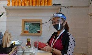Une femme suit les protocoles sanitaires en portant un masque facial au travail dans un restaurant en Indonésie.