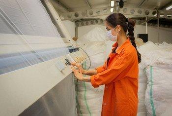 Une femme porte un masque facial lorsqu'elle travaille dans une entreprise textile à İzmir, en Turquie.