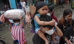 Pessoas evacuadas chegando a centro de acolhimento em Manila
