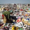 भारत में एक कूड़ा घर में कचरे में कुछ काम की चीज़ें बीनती एक महिला