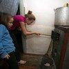 Alika, 11 ans, et sa soeur Sofia, âgée de 6 ans, mettent du charbon dans le poêle dans lleur maison de la colonie d'Olenivka, dans la région de Donetsk non contrôlée par le gouvernement ukrainien