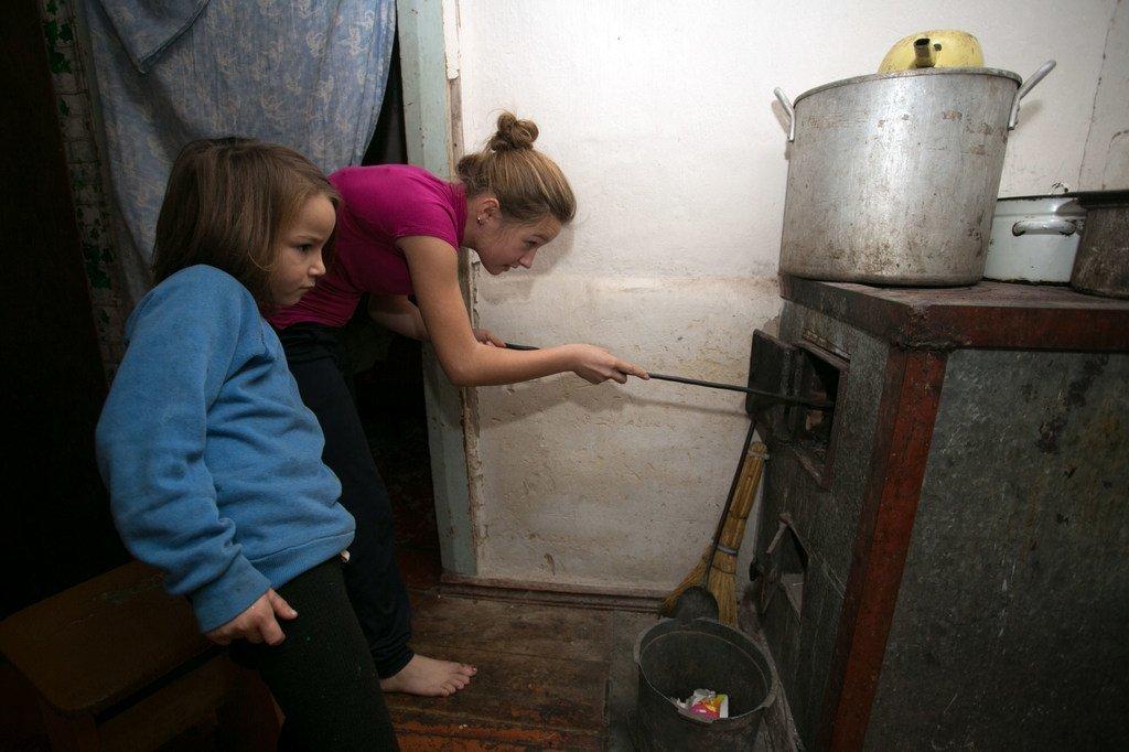 在乌克兰东部顿涅茨克地区非政府控制区的一所安置房里,11岁的艾莉卡(Alika)和她6岁的妹妹索菲亚(Sofia)正在往炉子里加煤。