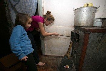 Alika, de 11 años, y Sofía, de 6, echan carbón a la estufa en su casa de Olenivka, en la región de Donetsk, Ucrania.
