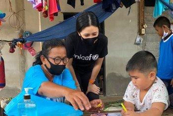 联合国儿童基金会的志愿者Rasa Pattikasemkul(中)与一个小男孩面对面互动,这在新冠封锁期间对这名男孩来说是一段十分珍贵的时光。