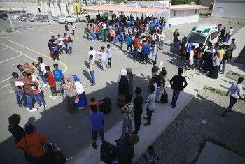 Los refugiados de Somalia, Siria y Eritrea que fueron  liberados de los centros de detención en Libia, pasan por el procedimiento de evacuación con el personal del Centro de Acogida y Partida del ACNUR en Trípoli, Libia.
