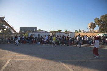 Des réfugiés de Somalie, de Syrie et d'Eritrée montent à bord d'un bus dans le centre d'hébergement du HCR à Tripoli, en Libye, en route pour un voyage en avion vers l'Italie.