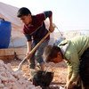 Children help their displaced families in Idlib governorate build shelters for protection against the cold at an informal settlement in Killi, near the border with Turkey.