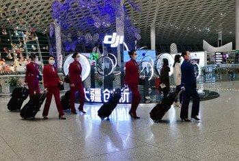 Wahudumu wa ndege wakiwa wamejikinga baada ya kutua katika uwanja wa ndege wa Shenzhen Bao'an nchini China