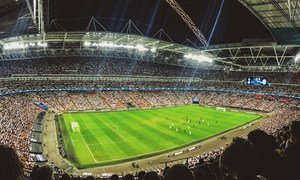 A crowd watching a football game inside Wembley Stadium in England.