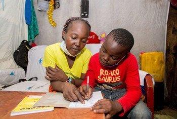 Un garçon de dix ans étudie avec l'aide de sa mère à la maison dans le quartier informel de Mathare à Nairobi, au Kenya.