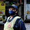 En Thaïlande, une agente chargée du nettoyage des espaces publics porte un masque facial tout en travaillant durant la pandémie de Covid-19.