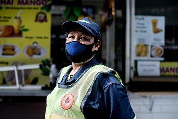 Una trabajadora de limpieza utiliza una mascarilla durante la pandemia de COVID-19 en Tailandia.