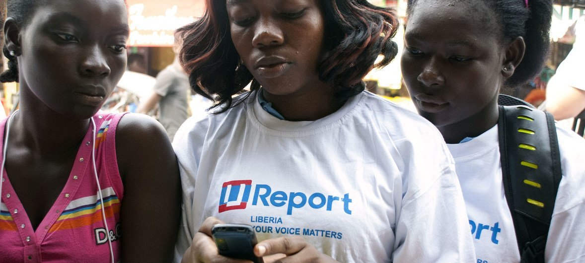 Adolescent girls in Liberia read information a mobile phone in the West Point neighbourhood of Monrovia, the capital.
