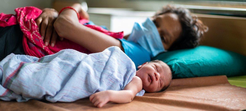 印度古吉拉特邦,新冠疫情期间,一位母亲戴着口罩与新生儿一同躺在医院的病床上。