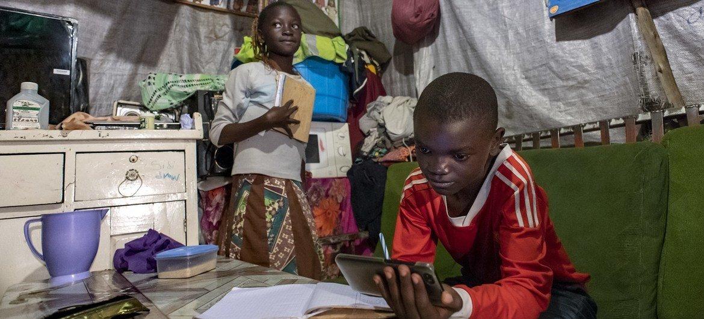 Samuel, 11 na mdogo wake wa kike Janet 10, wakisoma nyumbani kwao Mathare, Nairobi Kenya wakitumia meza pekee iliyoko ndani mwao na pia simu ya familia yao.