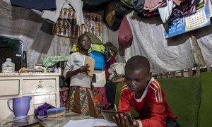 Samuel, 11 ans, et sa sœur Janet, 10 ans, étudient à l'unique table de leur maison à Mathare, Nairobi, Kenya, en utilisant le téléphone portable de la famille