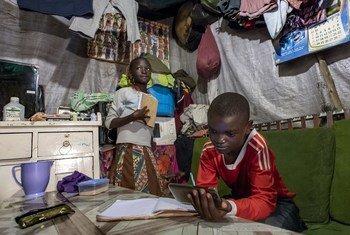 صاموئيل (11 عاما) وشقيقته جانيت (10 أعوام) يدرسان في منزلهما بنيروبي في كينيا ويستخدمات هاتف الأسرة المحمول.