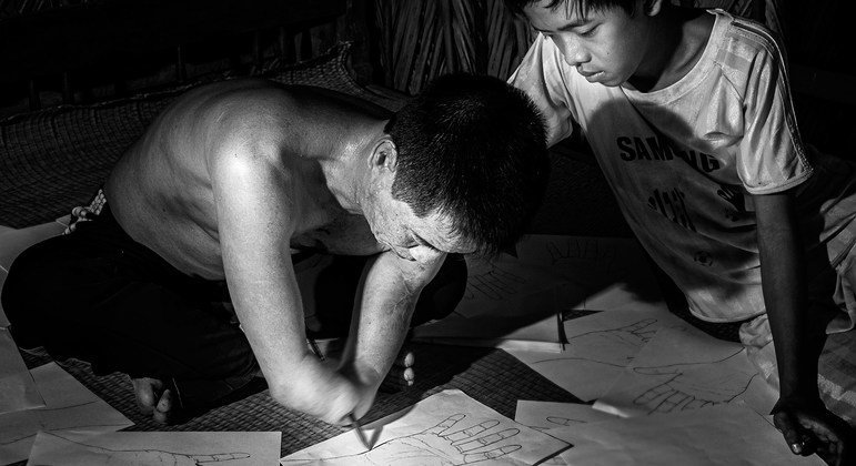 A boy in Viet Nam looks on as his father, whose lower arms were amputated sketches out hands on pieces of paper.