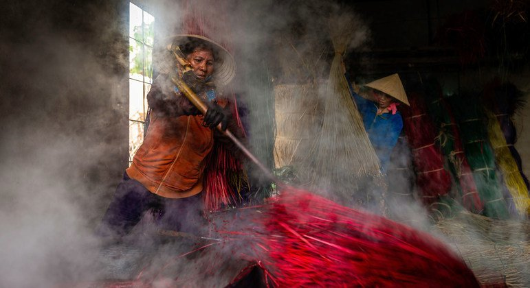 Two farmers in Viet Nam dye fibres they have cultivated.