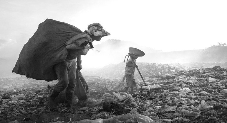 A child works alongside his mother picking through rubbish at a dump in Viet Nam.