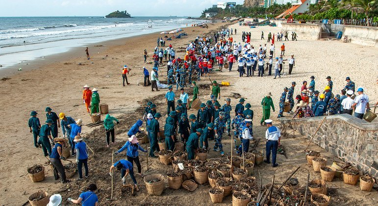A seaside community in a tourist area in Viet Nam gets together to collect rubbish from the sea.