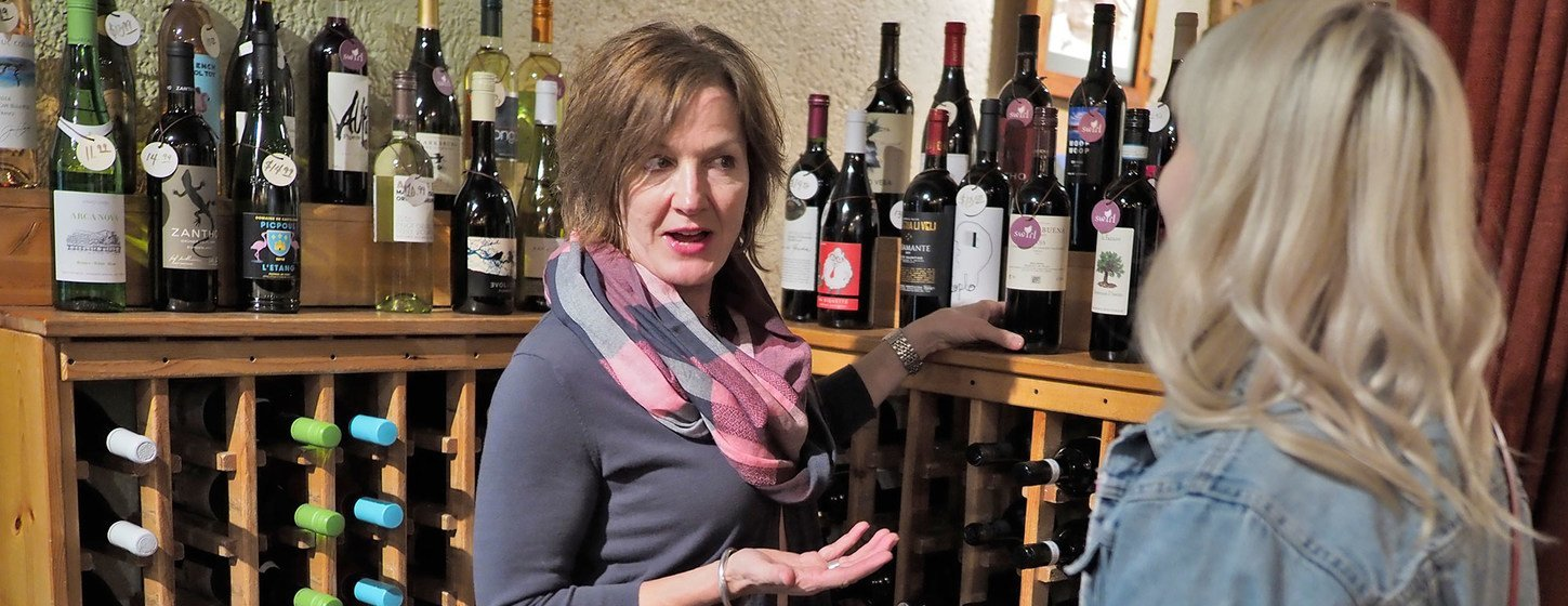 The owner of Swirl Wine Bar and Market New Orleans advises a customer about wine.