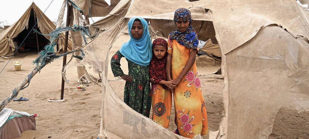 Displaced children stand in the shredded remains of tents in Abs settlement, Yemen, for internally displaced persons. Located just 40 km from the frontlines, the settlement is regularly damaged by passing sandstorms.