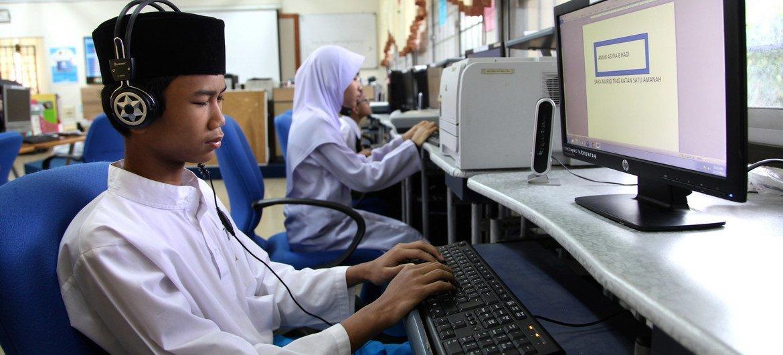 Adolescente usando software para operar computador em escola em Kuala Lumpur