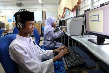 Un adolescent utilise un logiciel de synthèse vocale pour faire fonctionner un ordinateur dans une école spécialisée de Kuala Lumpur, en Malaisie.