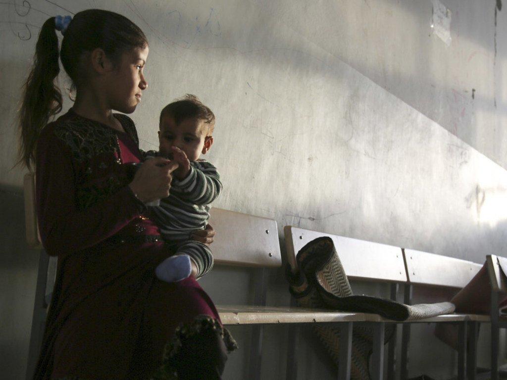 طفلة تحمل طفلا صغيرا وتجلس على مقعد في مدرسة تحولت إلى ملجأ في شمال الرقة في سوريا.