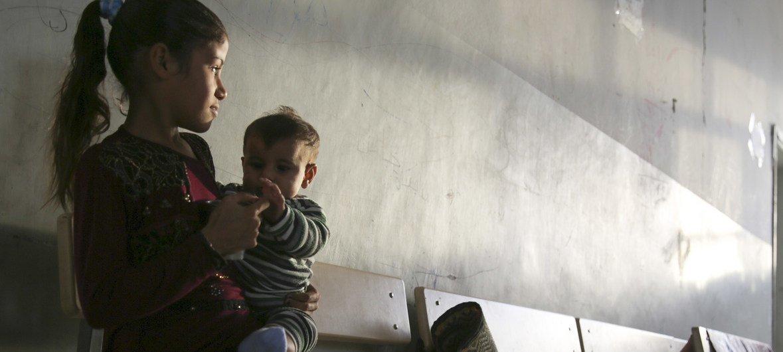 一个女童抱着一名幼儿,坐在叙利亚北部拉卡省一处用作避难所的学校内。2019年10月,叙利亚东北战事升级,导致超过10万8000名从哈塞克、拉卡和阿勒颇等地逃离家园以躲避战乱的百姓再次流离失所。