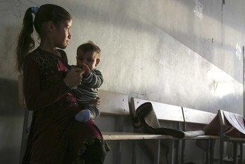 Une fillette tient un enfant assis sur un banc dans le couloir d'un abri transformé en école dans le nord d'Ar-Raqqa, en Syrie.