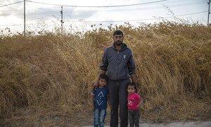 أب سوري مع طفليه في مخيم بردرش في دهوك العراق، بعد يوم من وصولهم.
