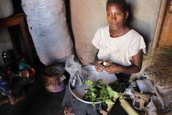 Scovia Atuhura Habibaana, mkimbizi kutoka Jamhuri ya Kidemokrasia ya Congo, DRC akiandaa mboga nyumbani kwake huko Hoima nchini Uganda.