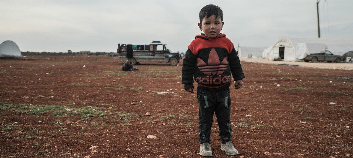 叙利亚西北部,一个男孩站在流离失所者营地内。