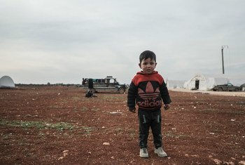 A young boy stands in a camp for people who have fled fighting in northwestern Syria.