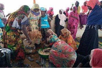 Walinda amani wanawake kutoka Tanzania walioko UNAMID wakifundisha wanawake wakazi wa Menawash jimboni Darfur nchini Sudan jinsi ya kupika kalmati na maandazi.