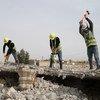 يقوم العمال بتقليص حجم الحطام إلى قطع أصغر لاستخدامها في كسارة الأحجار.